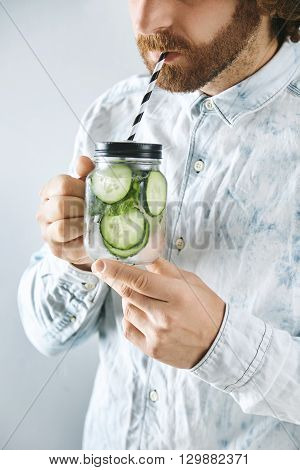 Unrecognizable Man In Light Jeans Shirt Drinks Fresh Home Made Cucumber With Mint Sparkling Lemonade