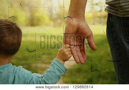 the parent holds the hand of a small child on piece of puzzle