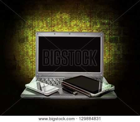 Laptop tablet smartphone and USB flash drive on the background of the glowing numbers of a matrix