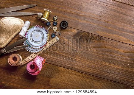 sewing tools and sewing kit on the wooden background
