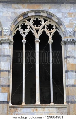 Gothic window with traceries on Monumental cemetery Composanto, Pisa, Italy