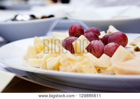cheese platter with grapes  light background. Selective focus