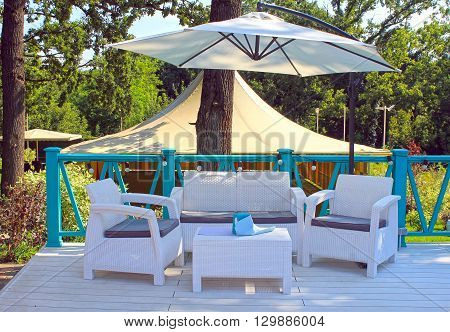 Al fresco cafe with white rattan wicker armchairs and tables on the summer garden terrace