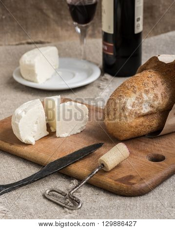 Bottle of wine cheese and white bread are on sacking