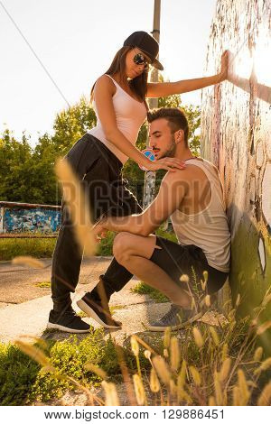A young HipHop styled couple standing against a wall in a urban environment.