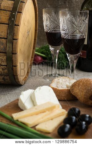 Two wineglasses olives cheese and white bread are on sacking