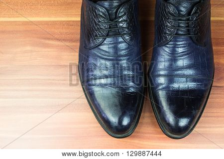 Classic men shoes on wood background close up