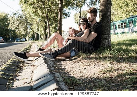 A young HipHop styled couple sitting next to a tree during sunset in a urban environment.