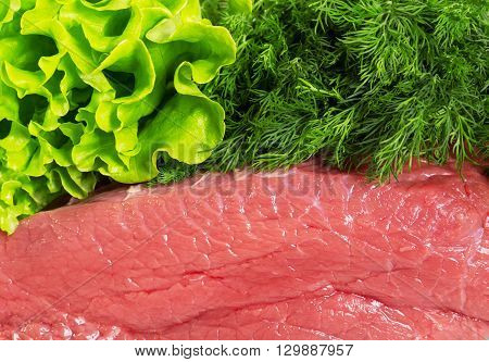 Meat fresh raw beef, dill and lettuce background.