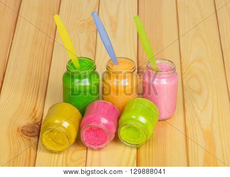 Jars of various baby food and spoons on a background of light wood.