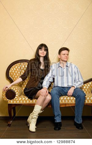 young beautiful woman and man sitting on sofa in room, man has put hand on knee to girl