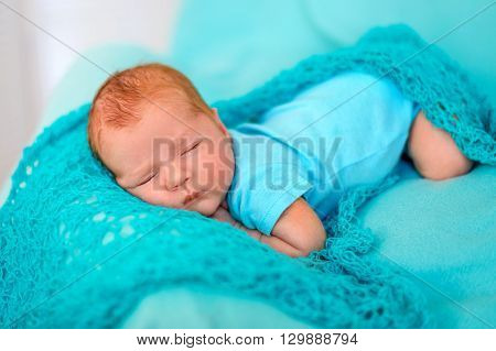 baby sleeping on the tummy on a blue blanket