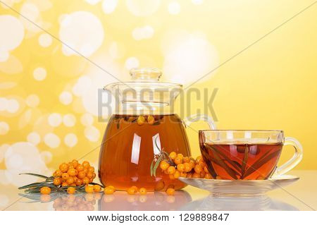Jug and cup and drink from the ripe berries of sea-buckthorn on abstract yellow background.