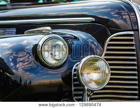 Close-up fragment of a black vintage car. Retro car. Headlights of vintage car. Selective focus.