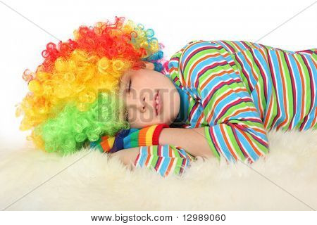 boy in clown dress sleeping isolated on white background