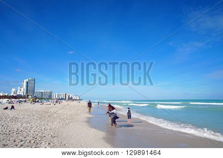MIAMI BEACH, UNITED STATES - FEBRUARY 8: People walk and relax at the sunny South Beach of Miami near Atlantic Ocean on 8th of February, 2016 in Miami Beach.
