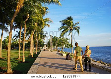MIAMI BEACH, UNITED STATES - FEBRUARY 8: People walk and relax at the sunny South Point Park of Miami near Atlantic Ocean on 8th of February, 2016 in Miami Beach.