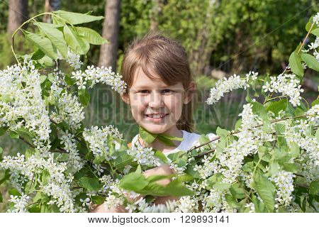 Girl smiling with a bouquet of bird cherry blossoms