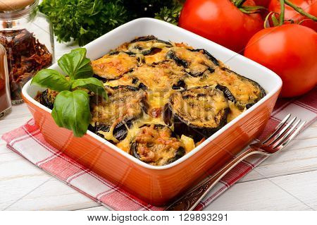 Moussaka - greek casserole with eggplants on wooden table.