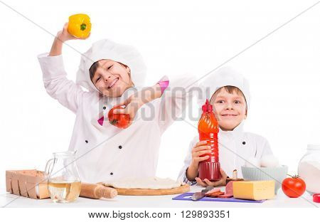 cute little boy and girl in white uniform with ingredients for pizza