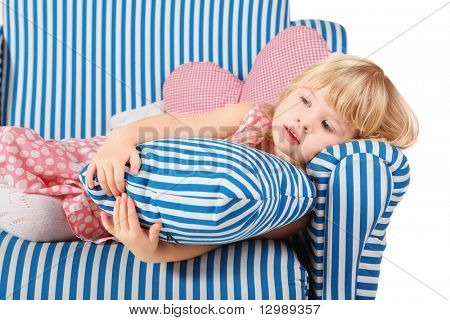 little girl wearing dress and shoes is lying on comfortable chair. cushion in girl's hands. isolated.
