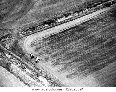 view from above on harvester plowing field, black and white photo