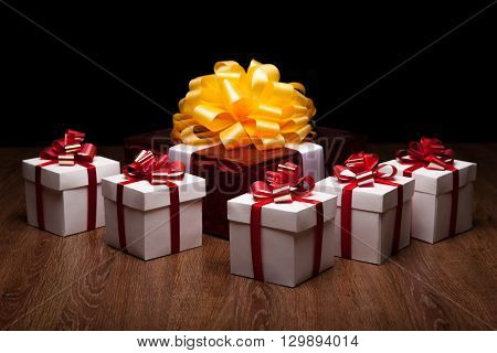 one large red gift box with yellow bow with small gift boxes on black background