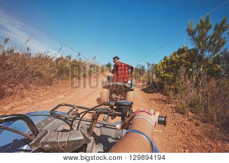 Young man driving a quad bike on country road. Young man on an all terrain vehicle in nature. POV shot.