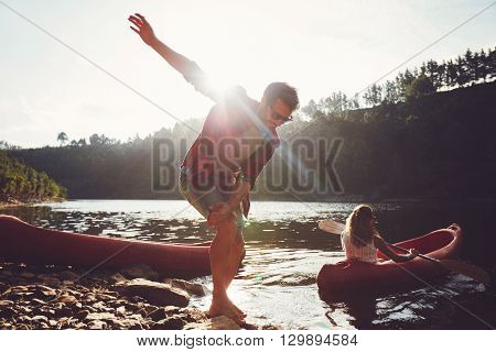Young Man On The Edge Of Lake With Woman Canoeing