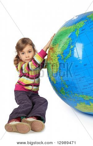 little girl sitting near big inflatable globe and holding it, looking at camera, isolated on white