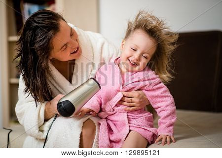 Mother drying hair of her little girl dressed in pink bathrobe