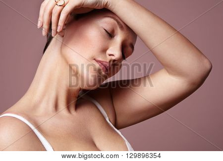 Woman Touching Forehead In A Pink Background