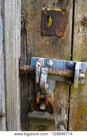 Old wood textured door and rusty iron doorlock close up
