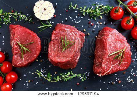 Fresh Raw Beef steak Mignon, with salt, peppercorns, thyme, garlic. Ready to cook