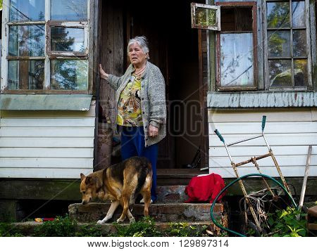 The old lady and the dog on the porch of the old village house