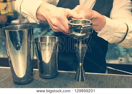 Bartender is squeezing citrus juice, toned
