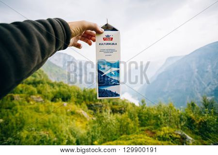 Aurland, Norway - August 2, 2014: Package curdled milk Kulturmjolk or sour from Tine in hand on background of Norwegian mountains. TINE SA is the largest Norwegian dairy product cooperative consisting of around 15, 000 farmers and 5, 600 employees
