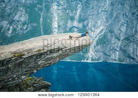 Odda, Norway - August 04, 2014: Young Man On Rock Clings To The Edge Of A Cliff And Looking Down In The Mountains Of Norway. Natural Attractions Of Trolltunga - Troll Tongue