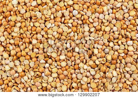 Close up dry yellow split peas background.
