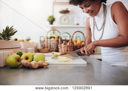 Young Woman Chopping Up Fresh Fruit For Smoothie