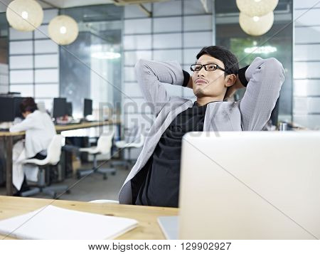 young asian business executive leaning back in a chair and thinking.