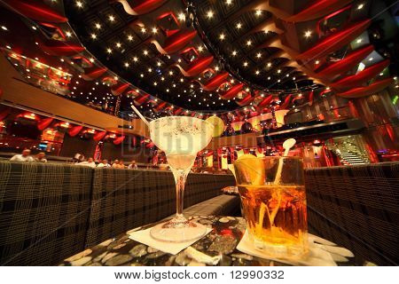 big illuminated hall. coaches and tables. wineglass and glass with drinks in center of image. focus on top of wineglass. people in out of focus. wide angle.