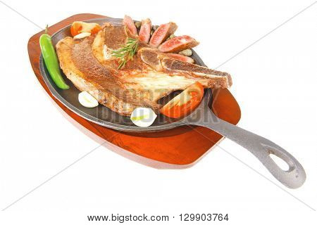 fresh roasted beef meat bone steak on metal iron plate with red hot pepper and tomatoes isolated on white background