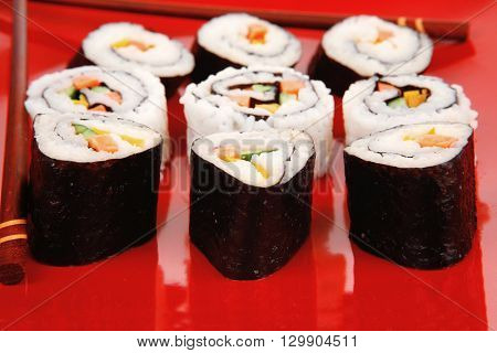 Japanese Traditional Cuisine - California Roll with Avocado and Salmon, Cream Cheese . on red dish with sticks isolated over white background