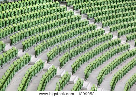 Rows of folded, green, plastic seats in very big, empty stadium.