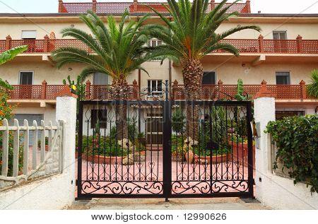 Forjado puerta negra del sanatorio. palmeras y edificios de sanatorio pueden verse fuera de puertas