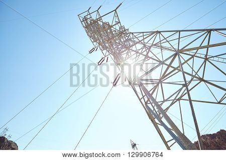 Electricity transmission tower against sun and blue sky.