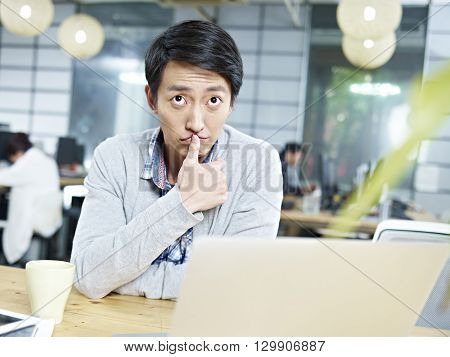 young asian business person sitting at desk thinking hard.