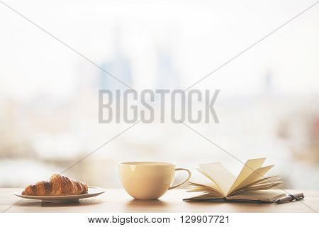 Desktop with round coffee mug croissant on plate and open book on blurry city background