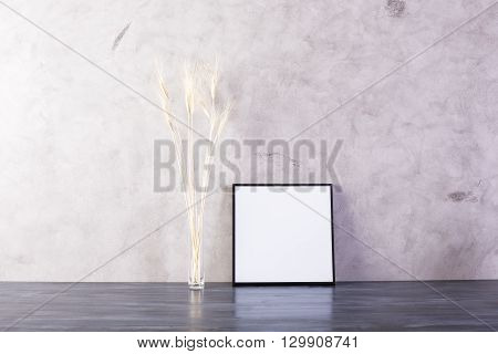 Small picture frame and wheat spikes on concrete background. Mock up